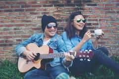 Человек битника играя гитару для его подруги внешней против br Стоковая Фотография RF