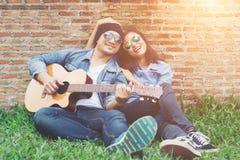 Человек битника играя гитару для его подруги внешней против br Стоковое Фото