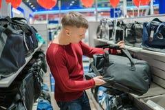 Человек битника покупая стильный рюкзак в магазине супермаркета стоковое фото rf