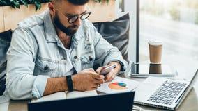 Человек битника сидит в кафе, использует smartphone, работает на 2 компьтер-книжках Бизнесмен читает сообщение информации в телеф стоковые изображения