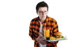 Человек болезни грустный молодой в рубашке положил руку на брюшко боли, боль в животе, положение и бургер удержания изолированный стоковая фотография