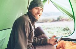 Человек бородатого путешественника теплый одетый использует его мобильный телефон стоковая фотография rf