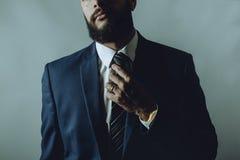 Человек бороды в костюме исправляет связь стоковая фотография rf