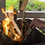 Человек бросает дерево в огонь Стоковая Фотография