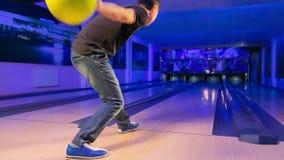 Человек бросает шарик боулинга на игровой площадке и стучает штырями сток-видео