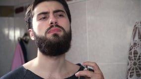Человек брызгает духи Конец вверх по красивому серьезному человеку squirting духи на шеи Человек в bathroom перед зеркалом акции видеоматериалы