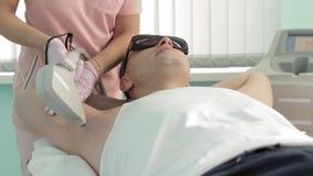 Человек брюнета в стеклах кладет на софу пока женский мастер делает волосы lazer underarm извлекая замедленное движение акции видеоматериалы
