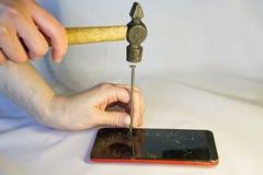 Человек бьет ноготь молотком в экран смартфона стоковое фото