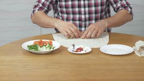 Человек варит shawarma на кухонном столе дома Пита, овощи и зеленый лук с соусом и майонезом конец сток-видео