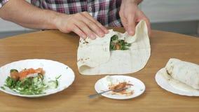 Человек варит shawarma на кухонном столе дома Пита, овощи и зеленый лук с соусом и майонезом конец акции видеоматериалы