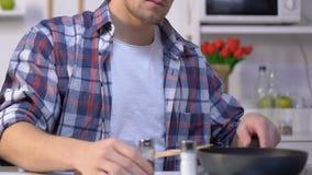 Человек варя завтрак, добавляющ земной перец в сковороду, приправляя блюдо видеоматериал