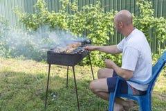 Человек варя мясо на барбекю Молодые пары делая барбекю в их саде Человек варя мясо на барбекю Стоковое Изображение