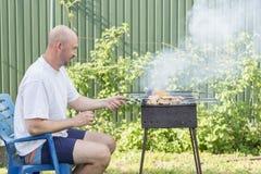 Человек варя мясо на барбекю Молодые пары делая барбекю в их саде Человек варя мясо на барбекю Стоковое Изображение RF