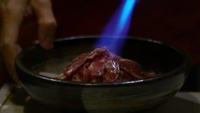 Человек варя с паяльной лампой огня свежее мясо в шаре на японском ресторане сток-видео