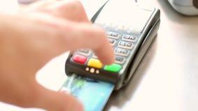 Человек вводит кредитную карточку в терминал, оплачивающ с кредитной карточкой и установил код PIN сток-видео