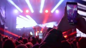 Человек вентилятора делает фото и видео на smartphone на рок-концерте в ярких мигающих огнях