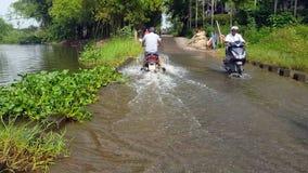 Человек взгляда задней стороны управляет мотоциклом вдоль дороги затопленной рекой акции видеоматериалы