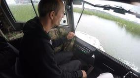 Человек взгляда со стороны замедленного движения управляет ховеркрафтом вдоль озера видеоматериал