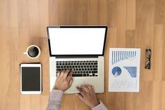 Человек взгляд сверху используемый рук компьтер-книжки на деревянных настольном компьютере и экземпляре Стоковые Фотографии RF