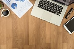 Человек взгляд сверху используемый рук компьтер-книжки на деревянных настольном компьютере и экземпляре Стоковое Изображение