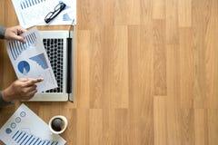 Человек взгляд сверху используемый рук компьтер-книжки на деревянных настольном компьютере и экземпляре Стоковое Изображение RF