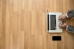 Человек взгляд сверху используемый рук компьтер-книжки на деревянных настольном компьютере и экземпляре Стоковое Фото
