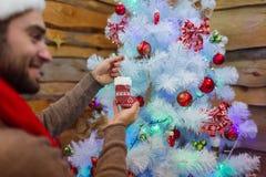 Человек висит рождественскую елку на декоративном дереве indoors стоковые фото