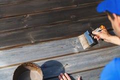 Человек восстанавливает деревянную палубу патио с деревянной защитной краской стоковые фото