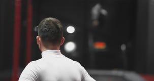 Человек во взгляде центрального защитника батута наблюдая, как другие люди поскакали на заднем плане видеоматериал
