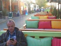 Человек во дне осени умного телефона пользы кафа патио теплом стоковое изображение