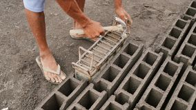 Человек вручную производит прессформы кирпича для конструкции от вулканического пепла в городе Legazpi philippines акции видеоматериалы