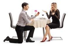 Человек вставая на колени и предлагая с кольцом к женщине на обеденном столе стоковые фото