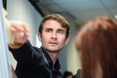 Человек вставляет примечание на афише в офисе стоковая фотография rf