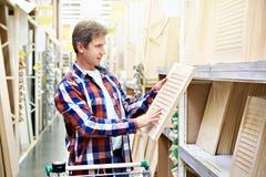 Человек выбирает деревянные фасады для мебели в магазине стоковое фото rf
