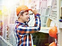 Человек выбирает защитный шлем в магазине стоковые фотографии rf