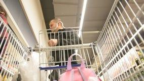 Человек выбирает плодоовощи Абстрактное неясное изображение торгового центра и людей Предпосылка взгляда магазинной тележкаи defo сток-видео