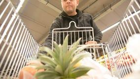 Человек выбирает плодоовощи торгового центра и людей Предпосылка взгляда магазинной тележкаи defocused с плодоовощ сток-видео