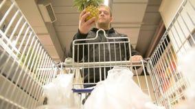Человек выбирает плодоовощи торгового центра и людей Предпосылка взгляда магазинной тележкаи defocused с плодоовощ акции видеоматериалы