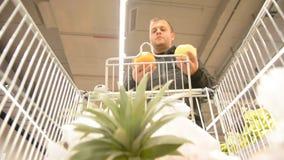Человек выбирает плодоовощи торгового центра и людей Предпосылка взгляда магазинной тележкаи defocused с плодоовощ видеоматериал