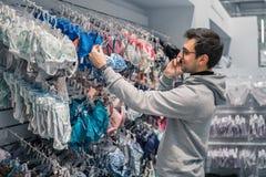 Человек выбирая нижнее белье женское бельё для его жены в магазине супермаркета Стоковое Изображение RF