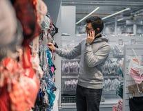 Человек выбирая нижнее белье женское бельё для его жены в магазине супермаркета Стоковые Изображения