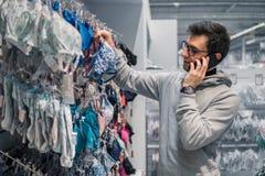 Человек выбирая нижнее белье женское бельё для его жены в магазине супермаркета Стоковые Фото