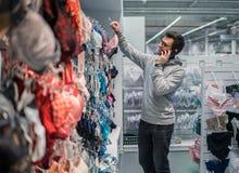 Человек выбирая нижнее белье женское бельё для его жены в магазине супермаркета Стоковые Фотографии RF