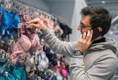 Человек выбирая нижнее белье женское бельё для его жены в магазине супермаркета Стоковое Изображение