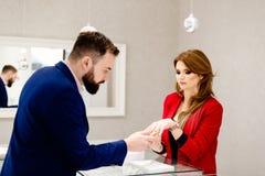 Человек выбирая обручальное кольцо в кольце ювелирных изделий Стоковые Изображения