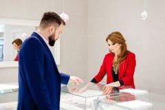 Человек выбирая обручальное кольцо в кольце ювелирных изделий Стоковые Изображения RF