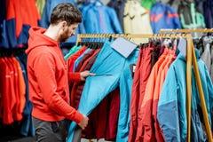 Человек выбирая одежды зимы в спортивном магазине стоковое фото rf
