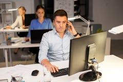 Человек вызывая на офисе смартфона вечером стоковое фото