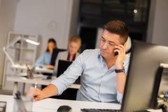 Человек вызывая на офисе смартфона вечером стоковое фото rf