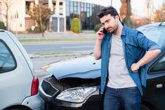 Человек вызывая обслуживание обочины после автокатастрофы стоковое фото